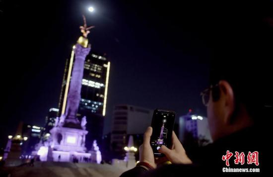 """当地时间2019年1月21日,欧美各地上演""""超级月亮"""",场面壮观。""""超级月亮""""是指处于近地点位置附近的满月,这时候的月亮看起来比它处于远地点时要更大、更亮。图为在墨西哥首都墨西哥城民众拍摄""""超级月亮""""天象。"""