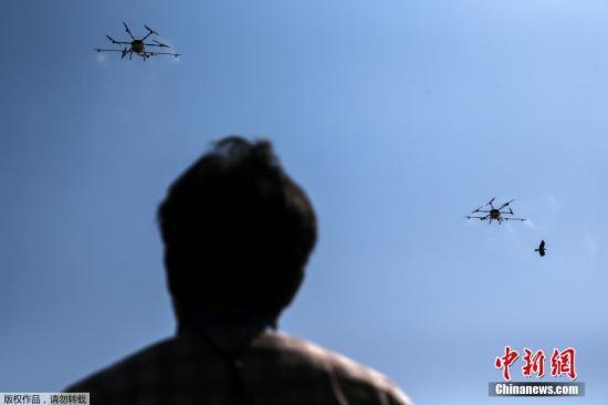 内地时间1月22日,泰国曼谷,无人机操纵者飞无人机在空中喷洒化学品,应对氛围污染。