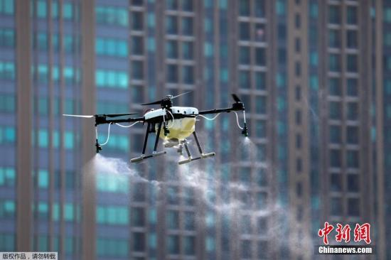 资料图片:当地时间2019年1月22日,泰国曼谷,无人机操作者飞无人机在空中喷洒化学品,应对空气污染。