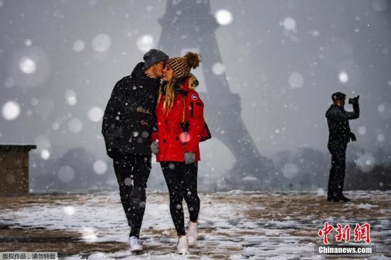 资料图:当地时间1月22日,法国巴黎市中心降下2019年第一场雪,气温也随之下降,街上的行人和车辆均有所减少。图为一对情侣在埃菲尔铁塔前合影留念。
