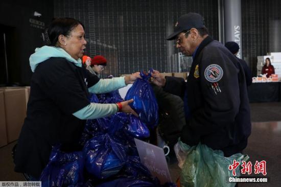 当地时间1月22日,美国纽约布鲁克林,运输安全管理局(TSA)的雇员在巴克莱中心领取免费食物。纽约食品银行正在为因政府关闭而受到影响的联邦工作人员分发食品。