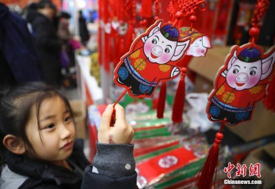 1月23日,正在北京全国农业展览馆举办的2019老北京年货大集人头攒动、热闹非凡。全国各地区优质特色产品及民俗文化在此一一呈现,给北京市民带来精彩纷呈的购物体验。图为小女孩被年货大集上的猪年福牌吸引。<a target='_blank' href='http://www.chinanews.com/'>中新社</a>记者 赵隽 摄