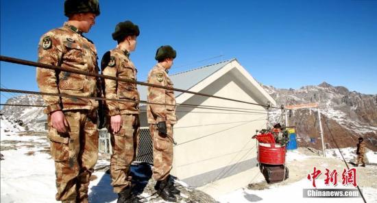 """2019年中国传统节日春节和藏历新年即异日临,坚守在中国西藏边防一线哨所的官兵们和去年相通,站在山顶遥看家园,幼心郑重守卫边关。在西藏数千公里边防线上的官兵们不及回家过年,他们照样在边境一线,把国家的领土""""装进""""视野,稳定守护着边关。图为位于雪山之巅的卓拉哨所,海拔4687米,由于山高坡陡,冬季车辆无法通走,所以被称为""""空中菜篮子""""的索道代替了公路,把哨所所需的物资,源源不息地运送到哨楼门口。中新社发 西藏军区供图"""