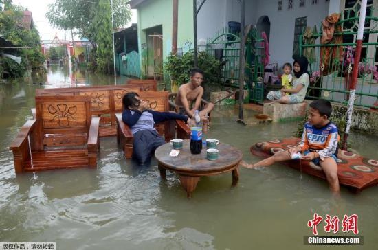资料图片:近日,暴雨袭击印尼苏拉威西岛南部,数十个小区被水淹没。图为当地时间1月25日,印尼南苏拉威西省望加锡的一居民区内,居民在清点家中财产。