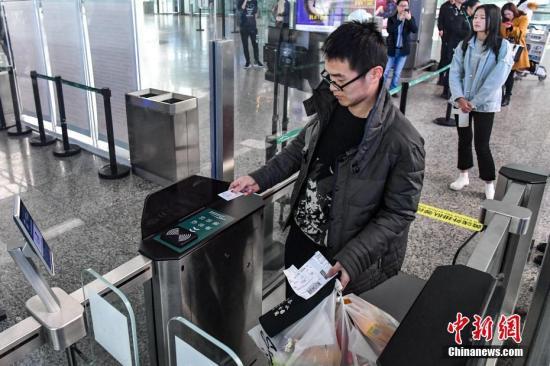 """1月25日,旅客通过""""自助智能安检通道""""进入候机楼。当日,广州白云机场在T1航站楼安检B区启用""""自助智能安检通道"""",该通道融合应用了人脸识别、人包对应、毫米波安全门及篮筐回传等技术。<a target='_blank' href='http://www.chinanews.com/'>中新社</a>记者 陈骥�F 摄"""