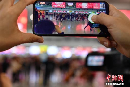 """1月27日,四川成都双流国际机场T2航站楼,旅客用手机记录""""快闪""""现场。当日,川港青少年在该机场玩""""快闪"""",嘹亮的歌声、优美的舞蹈、悠扬的琴声吸引来往的春运旅客驻足欣赏。中新社记者 刘忠俊 摄"""