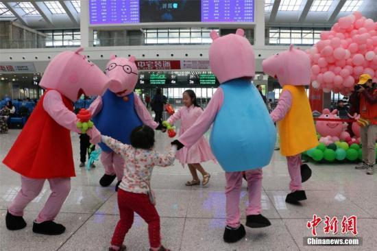 资料图:柳州火车站候车室里,小猪造型人偶与候车旅客玩耍。林馨 摄
