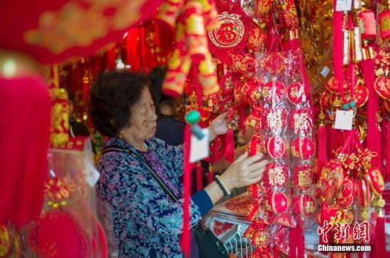 """1月28日,正值中国民间传统的""""小年"""",海南海口大街小巷的""""年味""""渐浓。海口博爱路是当地有名的年货一条街,各种对联、中国结、红包、红灯笼等吸引了众多市民及游客前来置办年货,迎接猪年新春的到来。图为市民选购年货。<a target='_blank' href='http://www.chinanews.com/'>中新社</a>记者 骆云飞 摄"""