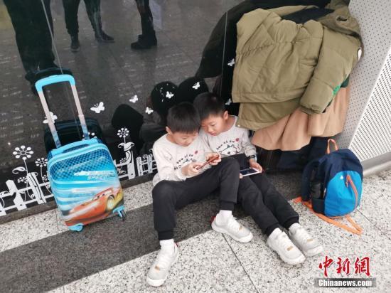 1月29日晚,深圳北站通报称,该站当天发送旅客21万人次。图为一对双胞胎候车时玩起手机。<a target='_blank' href='http://www.chinanews.com/'>中新社</a>记者 陈文 摄