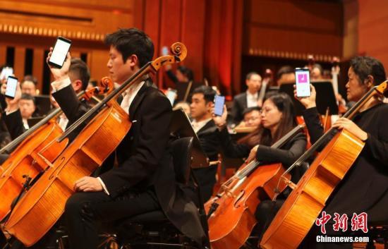 """当地时间1月29日,第五届中国—欧盟文化艺术节在布鲁塞尔拉开帷幕,知名音乐家谭盾指挥广州交响乐团奉献了一场中西合璧的精彩演出。图为音乐会尾声,谭盾还""""玩心不改"""",在返场曲目《风与鸟的密语》中加入手机数码音乐元素,舞台上的乐手一度纷纷举起自己的手机,令现场观众""""大开眼界""""。中新社记者 德永健 摄"""
