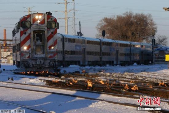 当地时间1月29日,一辆火车在燃起火苗的铁轨上驶向芝加哥市中心。