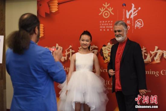 """在春节即将到来之际,当地时间1月30日晚,2019""""欢乐春节·魅力中国""""晚会在美国洛杉矶举行,为中美各界嘉宾带来一场精彩的文艺盛宴。14岁的北京女孩李溯(图中)是这场晚会最年轻的小演员,她精湛的钢琴独奏赢得全场掌声。图为身着红色唐装的美国与会嘉宾热情地同来自中国的李溯在晚会现场合影。<a target='_blank' href='http://www.chinanews.com/'>中新社</a>记者 张朔 摄"""