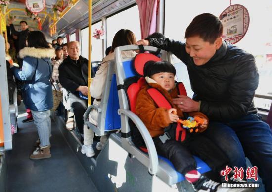 """河北邯郸26路公交车,小乘客坐在""""儿童安全座椅""""上。中新社记者 翟羽佳 摄"""