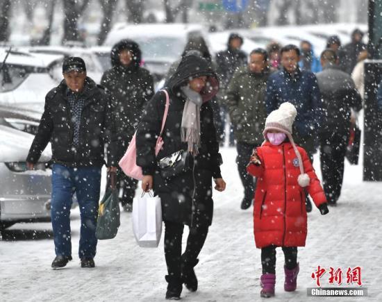 2月1日,新疆乌鲁木齐市迎来降雪天气。图为民众在纷纷扬扬的雪中出行。中新社记者 刘新 摄