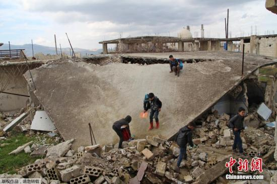 当地时间2019年1月30日,叙利亚伊德利卜Jisr al-Shughur,当地一学校遭炮击,学生在受损的教室和操场学习和玩乐。