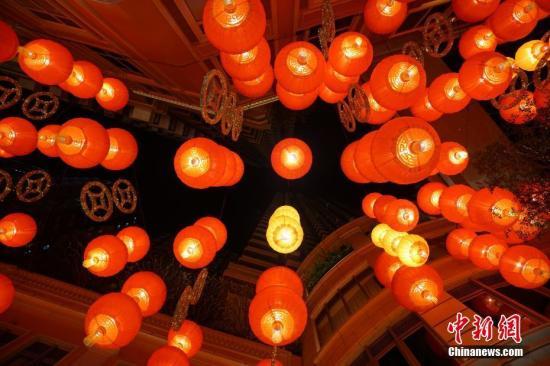 """1月31日晚,农历己亥猪年临近,香港湾仔利东街被打造成全港最大的户外新春步行街,668个寓意圆满的红灯笼和238个金光闪闪的金钱高悬街头,中庭一头硕大的红色""""喜盈猪""""喜气洋洋,寓意""""猪牵富裕年""""的新春步行街吸引越来越多的市民和游客前来沾喜气。 中新社记者 张炜 摄"""