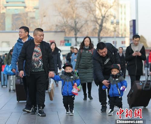 2月1日,北京站前的旅客行色匆匆。中国铁路总公司表示,1日,铁路春运客流保持高位运行,全国铁路预计发送旅客1050万人次,同比增长10.1%;铁路部门持续提升运力,预计加开旅客列车1004列。中新社记者 贾天勇 摄