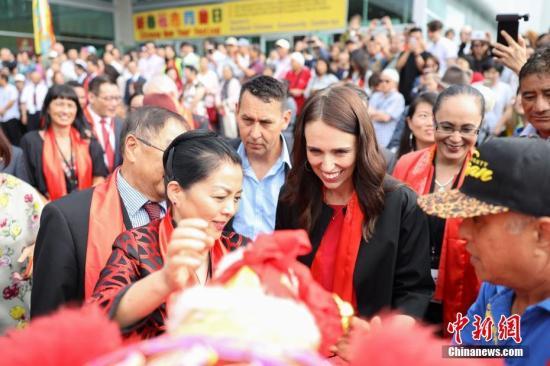 """2月2日,作为新西兰奥克兰市一年一度最具人气的中国新年庆祝活动——2019""""欢乐春节""""新春花市同乐日活动在奥克兰ASB会展中心开幕,近5万名华侨华人与当地居民共同感受中国新年的热闹气氛。图为中国驻奥克兰总领事许尔文(左一)与新西兰总理杰辛达·阿德恩共同为花市舞狮团雄狮挂上节日绣球。中新社发 张健勇 摄"""