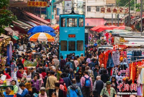 2月3日是农历十二月二十九日,一辆叮叮车正缓缓驶入位于香港北角的春秧街露天街市。这里人头攒动,各种年货琳琅满目,众多市民前来购买年货。电车司机面对如潮人群,也不急于向前,常常停下来等待人群离开路轨才慢慢向前行驶。春秧街有近百年的历史,是香港著名的特色街市,因叮叮车驶入露天市集的奇特景观而被香港旅发局推介成香港旅游景点之一,吸引不少内地以及世界各地游客观光。中新社记者 张炜 摄