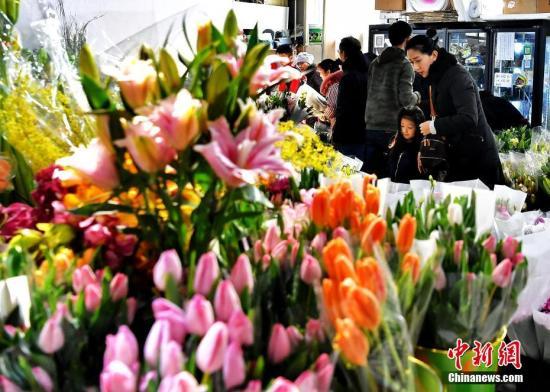 资料图:市民购置花卉装扮居室。中新社记者 刘新 摄