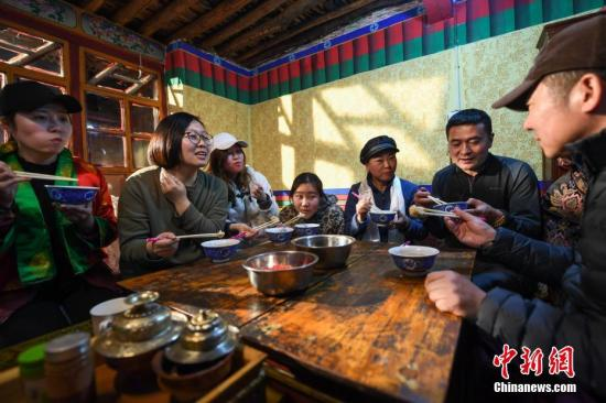 资料图:游客们在藏民家中迎接藏历新年。图/何蓬磊