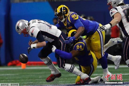 """资料图:2019年第53届美国职业橄榄球大(NFL)年度冠军赛""""超级碗""""比赛中,新英格兰爱国者队的汤姆·布雷迪(Tom Brady)在洛杉矶公羊队John Franklin-Myers (94) 阻止下进攻。"""