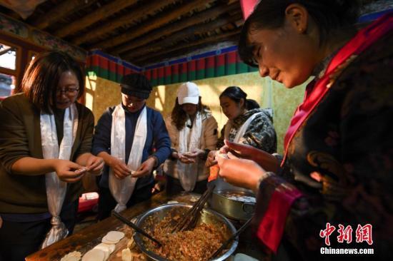 游客们在德吉家中包饺子,迎接藏历新年。 图/何蓬磊