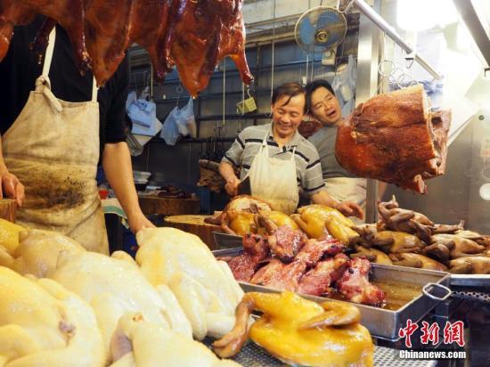2月4日,农历年除夕,香港市民纷纷一早选购年货,准备欢度除夕夜,在东区筲箕湾一街市,烧腊专卖店生意红火,老板伙计们笑逐颜开。中新社记者 洪少葵 摄