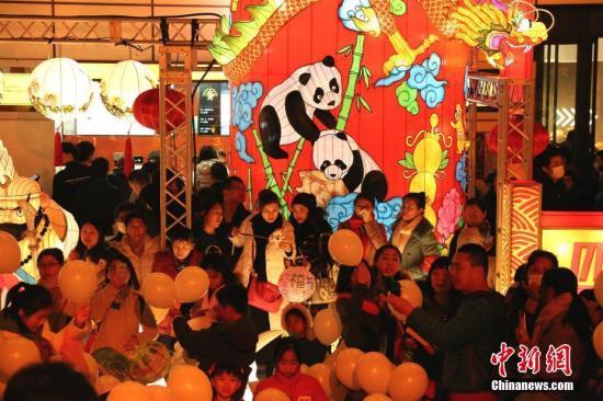 """2月4日晚,日本著名地标性建筑东京塔首次点亮""""中国红""""。现场还布置了来自四川自贡的新春彩灯,吸引游客驻足。中新社记者 吕少威 摄"""