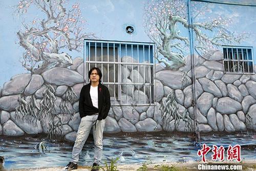 图为梁全威与画室合影。他曾花三个月时间,将贵州风景涂鸦在画室外墙。中新社记者 陈小愿 摄