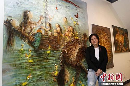 """图为梁全威介绍""""两岸婚姻""""主题的作品。中新社记者 陈小愿 摄"""