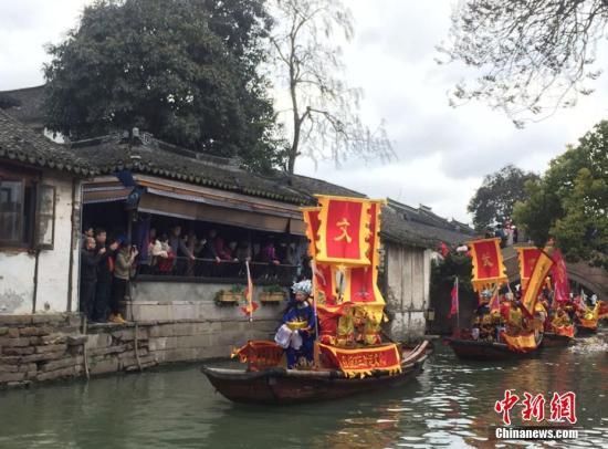 """游人们争睹着""""财神""""乘坐摇橹船,沿着水上财道,穿过古桥,走街串巷。 黄莹 摄"""