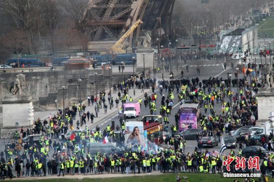 """当地时间2月9日,巴黎遭遇自2018年11月以来的第13轮""""黄背心""""运动示威,示威者在埃菲尔铁塔下集聚。中新网记者 李洋 摄"""
