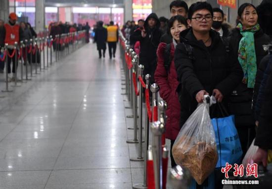 在阜阳火车站,来自临泉的小伙子张强带着家乡的特产踏上回上海的列车。 韩苏原 摄