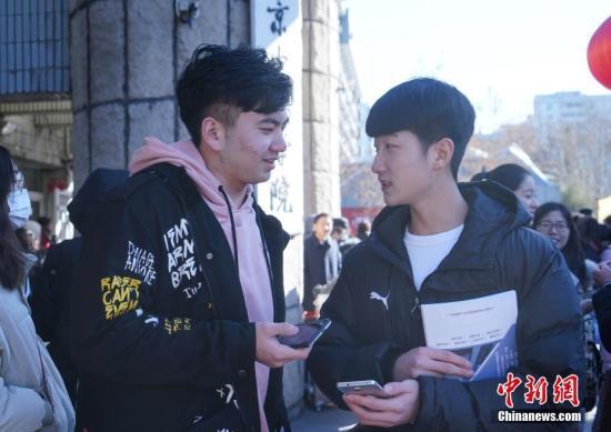 2月16日,北京电影学院艺考拉开序幕。图为两名考生考试结束后在校门外交谈。中新社记者 张兴龙 摄
