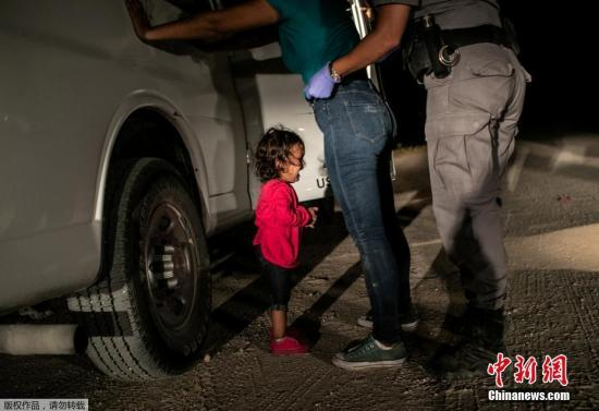 """本地工夫2018年6月12日,好国德克萨斯州麦卡伦,一位两岁洪皆推斯小女孩取妈妈正在好朱疆域被阻拦。按照特朗普当局的""""整容忍""""移平易近政策,好国疆域法律职员从本年4月起头,正在拘捕不法出境者时强迫别离其已成年后代,一切被拘捕的不法出境者,城市被闭押进狱面对审讯以至遣返,正在那一过程当中将其后代另止安设,报酬制作""""骨血别离""""喜剧,遭到各圆攻讦。"""