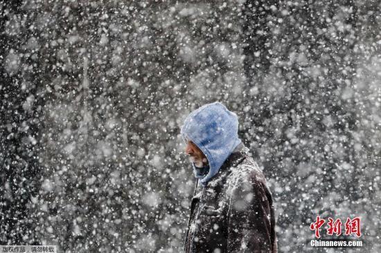 弗吉尼亚的天气预报中心预测,当地在20日会有几英尺的降雪,之后将会伴随雨夹雪和霜冻。图为行人走在暴风雪肆掠的费城街头。