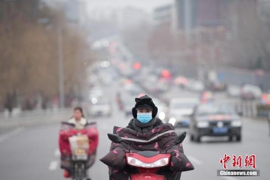 资料图:市民戴口罩出行。中新社记者 韦亮 摄