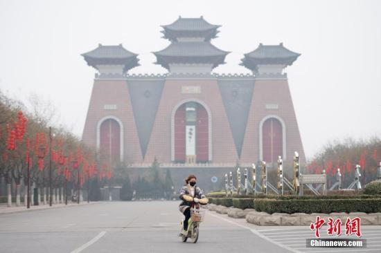 """资料图:山西省临汾市,市民戴口罩经过当地地标建筑""""华门""""。中新社记者 韦亮 摄"""