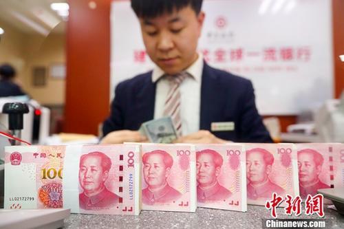 2月26日,山西省太原市一银行工作人员清点货币。当日,人民币对美元汇率中间价在实现连续六天上调后涨破了6.7关口。中国外汇交易中心公布的人民币对美元汇率中间价报6.6952,较前一交易日上调了179个基点,创逾七个月来新高。中新社记者 张云 摄