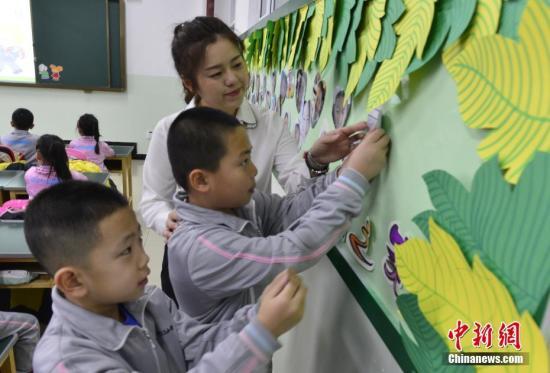 2月27日,新疆乌鲁木齐市第133小学,一年级的学生在老师的指导下将自己的照片贴上笑脸墙。当天,该市52万名中小学生结束假期生活,走进课堂开始新学期第一天的课程。中新社记者 刘新 摄