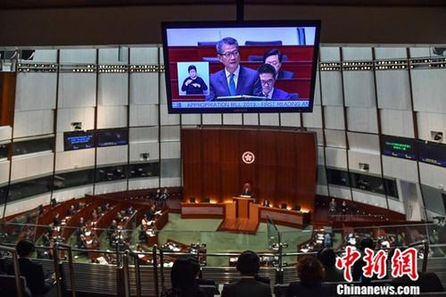 """资料图:2月27日,香港特区财政司司长陈茂波于立法会宣读新一年度财政预算案。陈茂波表示,预算案的大方向是""""撑企业、保就业、稳经济、利民生"""",将动用合共1500亿港元新资源。图为财政预算案发布现场。<a target='_blank' href='http://www.chinanews.com/'>中新社</a>记者 麦尚�F 摄"""