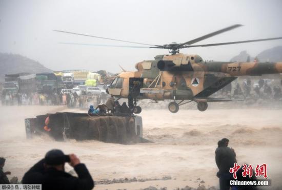 当地时间3月2日,阿富汗坎大哈省阿尔甘达卜地区,阿富汗士兵在洪水泛滥地区营救灾民。阿富汗南部坎大哈省的山洪暴发已造成至少20人死亡,数千所房屋遭到损毁。图为山洪中一辆卡车翻覆,阿富汗军方动用直升机救人。