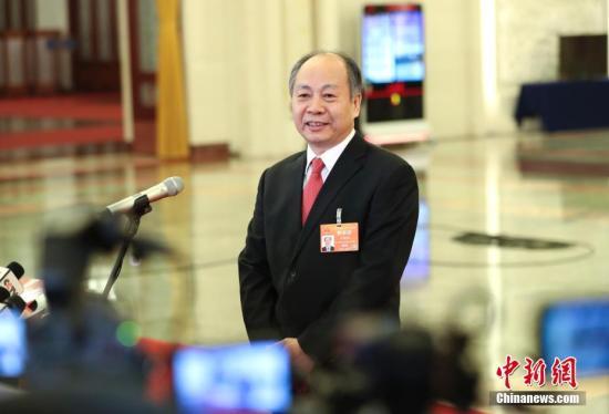 """3月3日,中国人民政治协商会议第十三届全国委员会第二次会议在北京人民大会堂开幕。图为国家国际发展合作署署长王晓涛在""""部长通道""""接受采访。 中新社记者 刘震 摄"""
