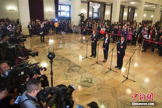 """3月5日,十三届全国人大二次会议在北京人民大会堂开幕。图为全国人大代表马善祥、程桔、党永富(从左至右)在""""代表通道""""接受采访。中新社记者 王骏 摄"""