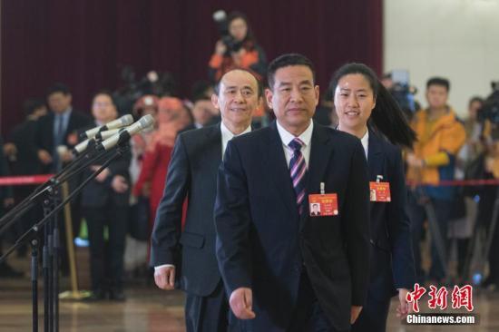 """3月5日,十三届全国人大二次会议在北京人民大会堂开幕。图为全国人大代表马善祥(左)、程桔(右)、党永富(中)在""""代表通道""""。<a target='_blank' href='http://www.qfhfbh.com/'>中新社</a>记者 王骏 摄"""