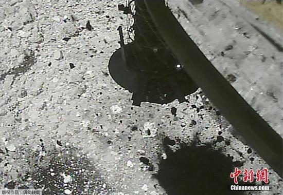 """资料图:当地时间3月6日,日本宇宙航空研究开发机构公布隼鸟2号探测器着陆小行星""""龙宫""""和采集样品的画面。图为隼鸟2号探测器向""""龙宫""""表面发射子弹以搜集小行星岩石和沙尘。"""
