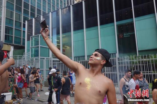 资料图:民众使用手机拍摄。中新社记者 莫成雄 摄