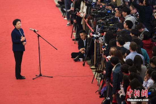 """3月8日,十三届全国人大二次会议在北京人民大会堂举行第二次全体会议。图为中国气象局局长刘雅鸣在""""部长通道""""接受采访。中新社记者 王骏 摄"""
