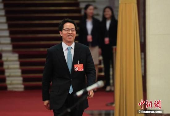 """3月8日,十三届全国人大二次会议在北京人民大会堂举行第二次全体会议。图为国务院港澳事务办公室主任张晓明步入""""部长通道""""接受采访。中新社记者 杜洋 摄"""